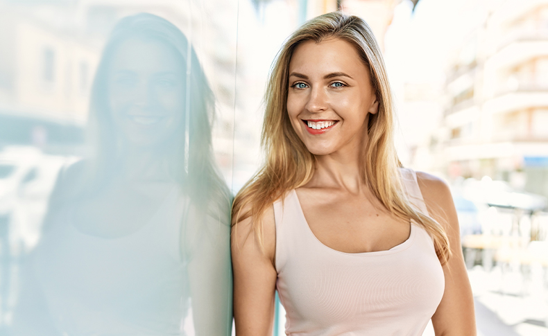 woman smiling and leaning against wall outside