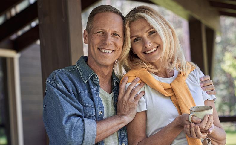 man and woman holding mug smiling outside