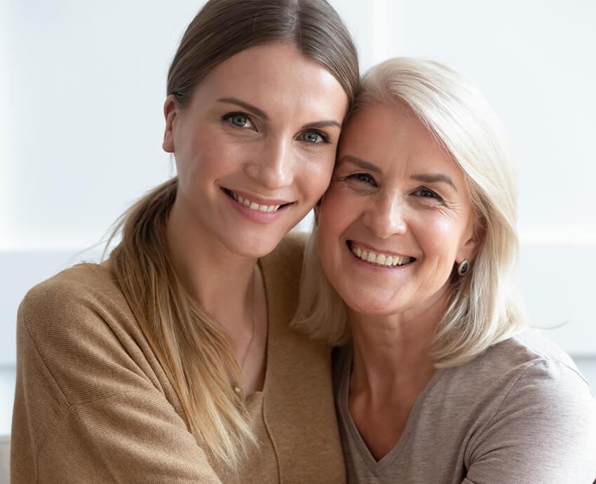 two women cheek to cheek smiling