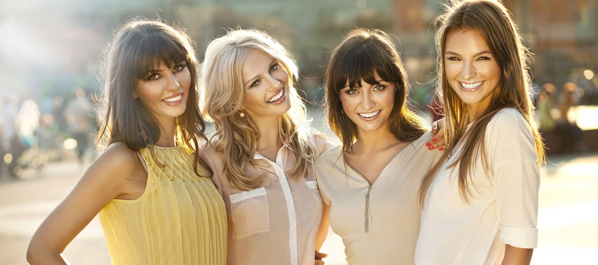 four women smiling outside