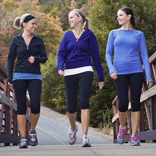 three women talking and walking outside