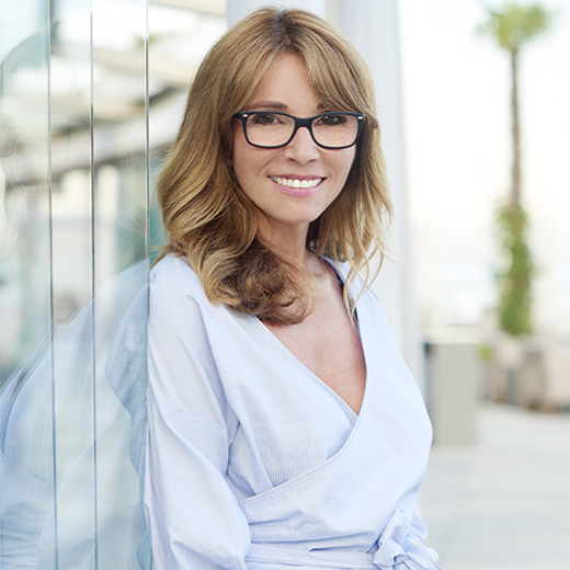 woman in glasses leaning on glass outside