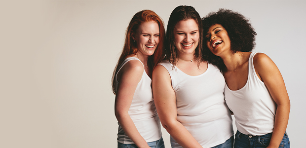 three women laughing in white tank tops and blue jeans