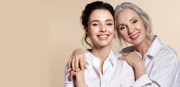 two women smiling in front of background