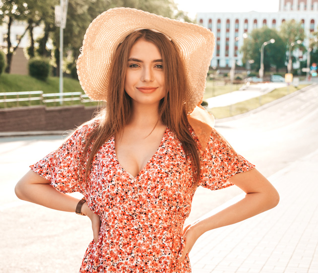 Woman smiling with hat on in the city